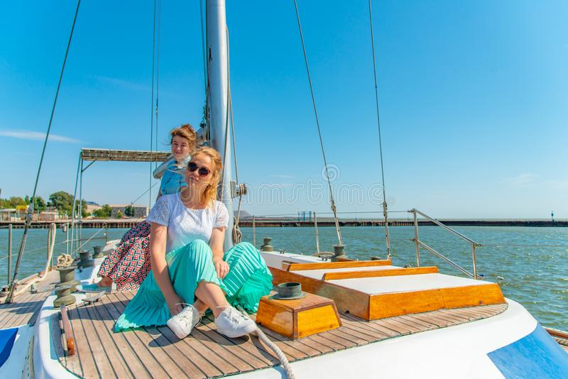 Duas meninas sentam-se em um iate na plataforma perto do mastro e olham-se para fora no mar imagens de stock