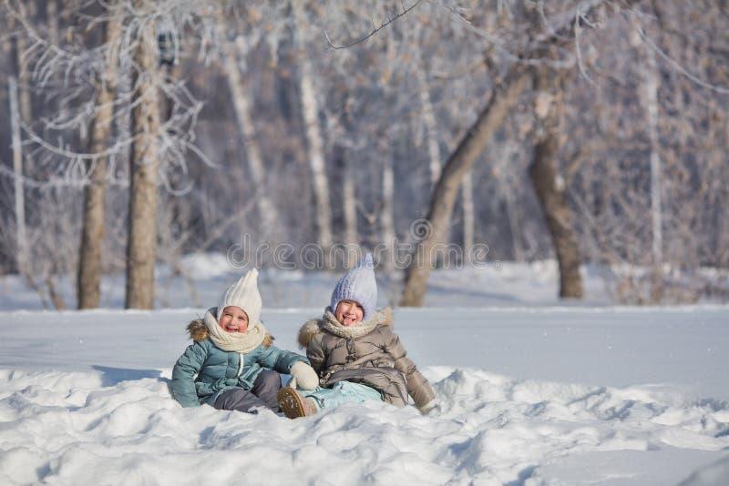 Duas meninas sentam-se no monte de neve e no tolo no inverno fotos de stock royalty free
