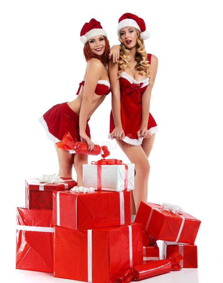 Duas meninas 'sexy' do Natal que levantam com uma pilha dos presentes imagem de stock royalty free