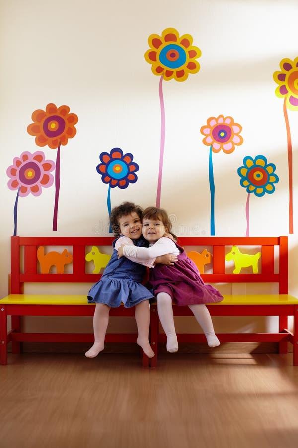 Duas meninas sorriso e hug na escola imagem de stock royalty free