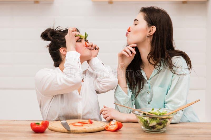 Duas meninas têm o divertimento com as folhas da alface como as sobrancelhas fotos de stock