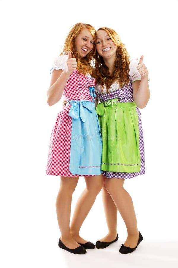 Duas meninas vestidas bávaras felizes que mostram os polegares acima
