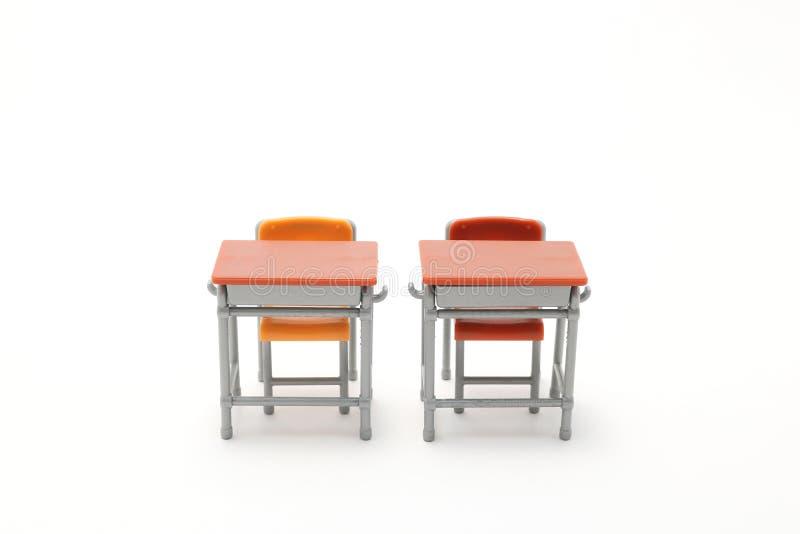 Duas mesas diminutas da escola no fundo branco fotos de stock