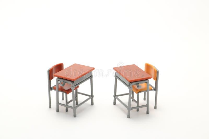 Duas mesas diminutas da escola no fundo branco fotografia de stock