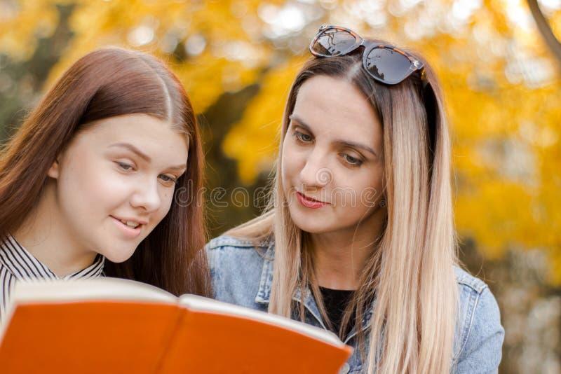 Duas moças bonitas, com prazer, leram um livro no parque do outono fotografia de stock royalty free