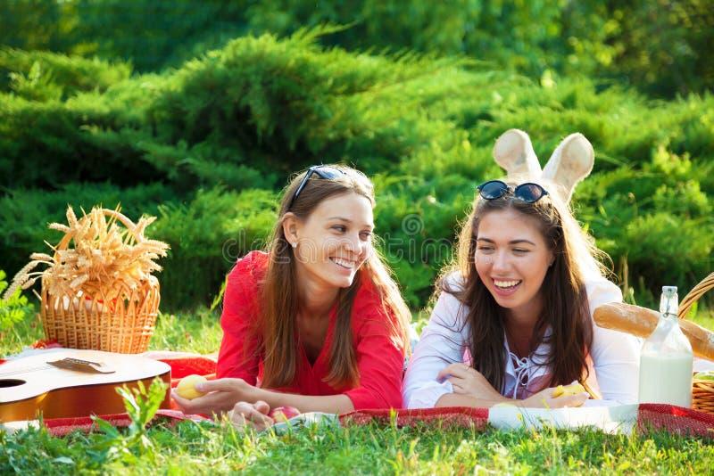 Duas moças bonitas em um piquenique no verão no parque que tem o divertimento e a fala foto de stock