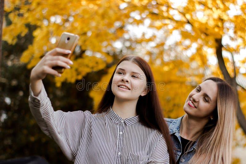 Duas moças de sorriso bonitas que tomam o selfie no telefone no parque do outono imagem de stock