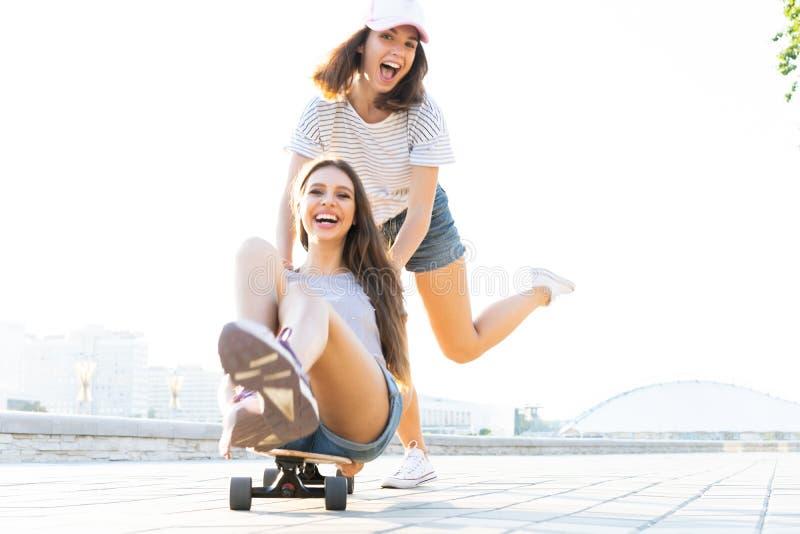 Duas moças de sorriso que têm o divertimento ao montar em um skate no parque fotografia de stock royalty free