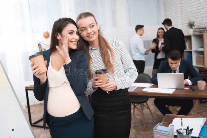 Duas moças estão espalhando a bisbolhetice na ruptura de café Bisbolhetice no escritório foto de stock