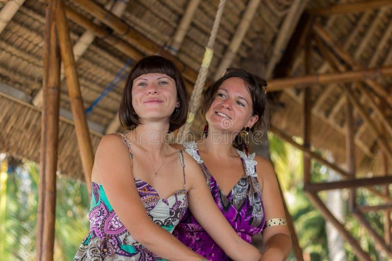 Duas moças felizes bonitas que sentam-se em um miradouro de madeira no dia ensolarado e tendo o divertimento, o sorriso e o riso  imagem de stock