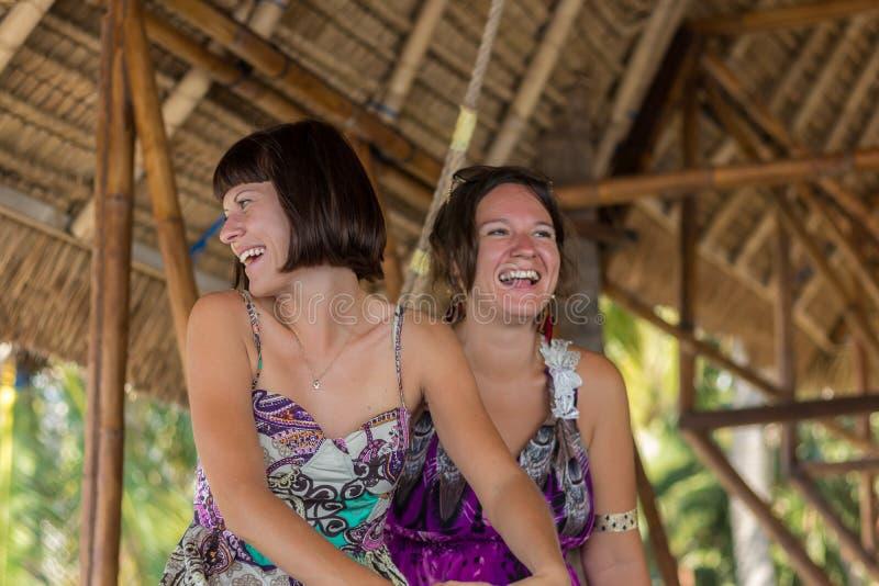 Duas moças felizes bonitas que sentam-se em um miradouro de madeira no dia ensolarado e tendo o divertimento, o sorriso e o riso  foto de stock royalty free