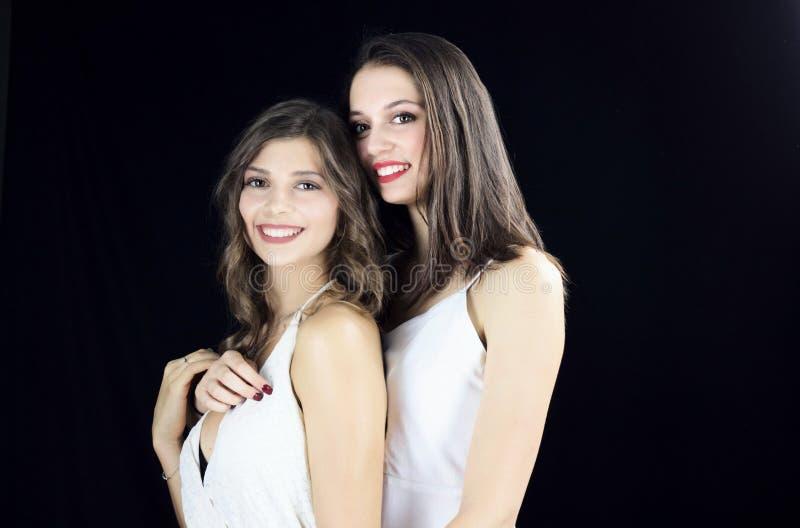 Duas moças felizes vestidas no branco fotografia de stock