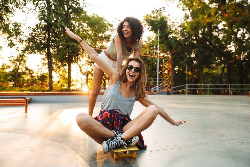 Duas moças positivas que têm o divertimento ao montar foto de stock royalty free
