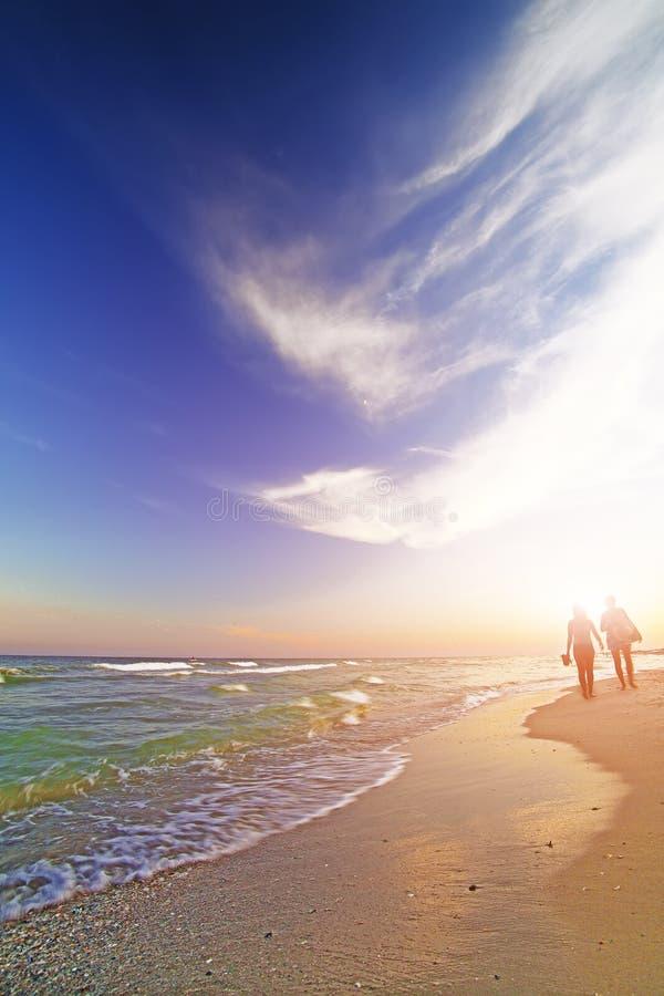 Duas moças que andam ao longo da costa no por do sol fotografia de stock
