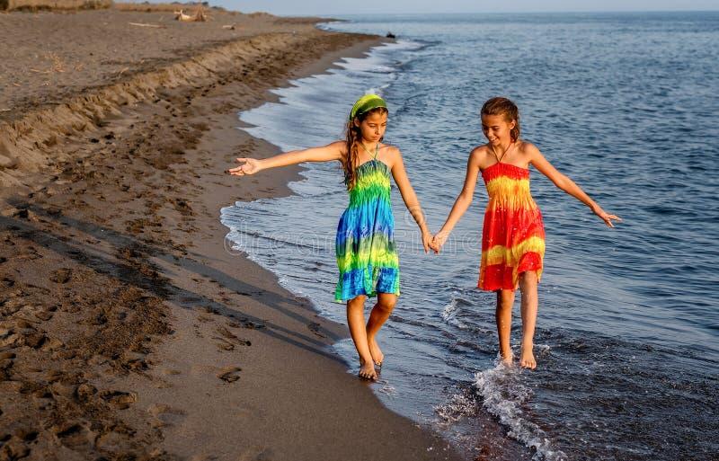 Duas moças que andam junto na praia fotografia de stock