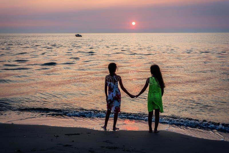 Duas moças que andam junto na praia no por do sol imagem de stock royalty free
