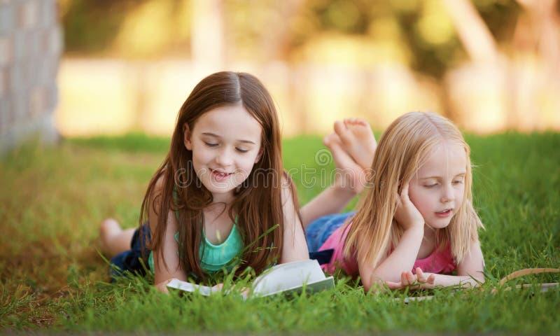 Duas moças que encontram-se na grama que lê fora um livro.   foto de stock