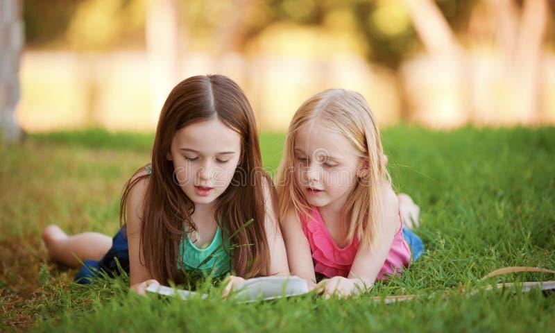 Duas moças que encontram-se na grama que lê fora um livro.   imagens de stock