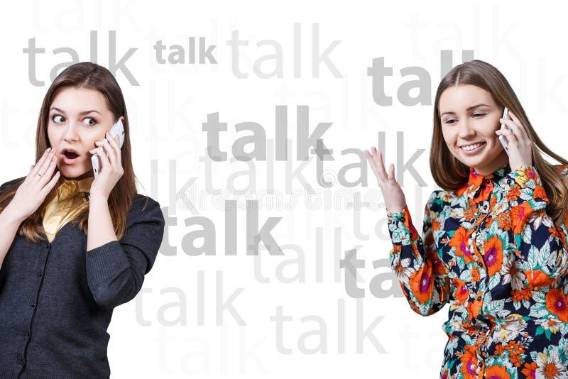 Duas moças que falam por telefones celulares fotografia de stock