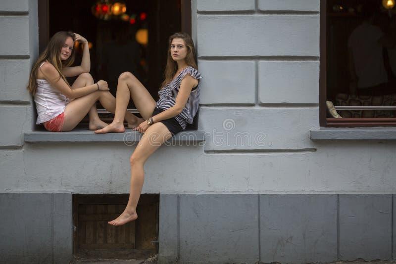 Duas moças que sentam-se na soleira que o clube noturno na noite cronometra imagem de stock royalty free