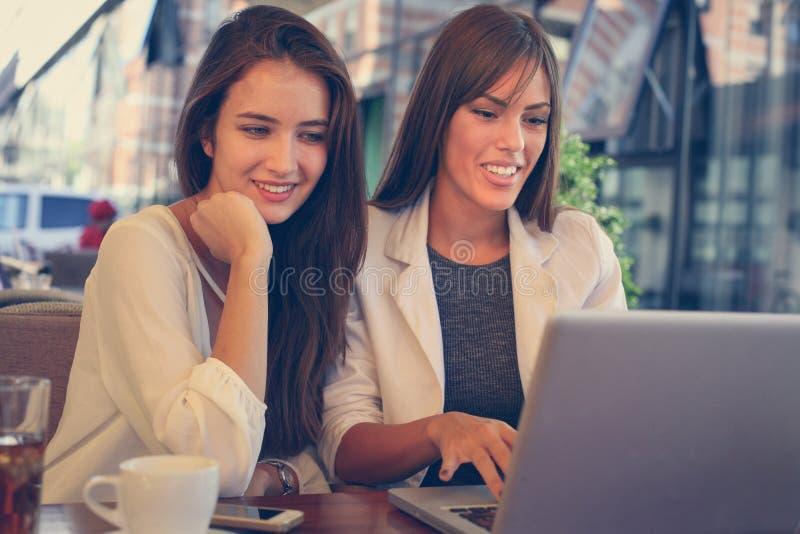 Duas moças que sentam-se no café usando o portátil imagem de stock royalty free