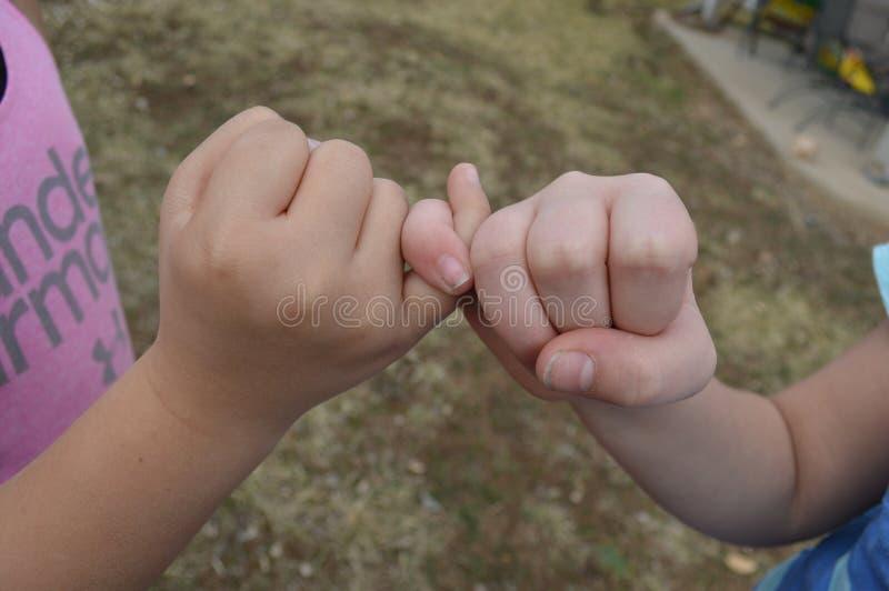Duas moças que travam os dedos mindinhos - melhores amigos fotografia de stock