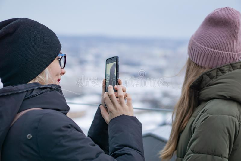 Duas moças são fotografadas na plataforma de observação no fundo da cidade velha em uma vista aérea imagem de stock