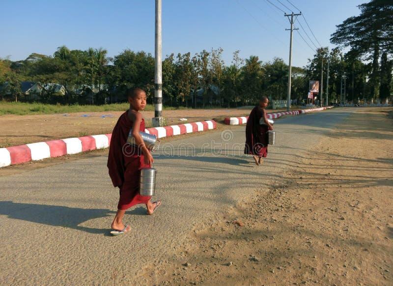 Duas monges budistas da criança que andam ao longo da estrada em vestuários vermelhos imagem de stock