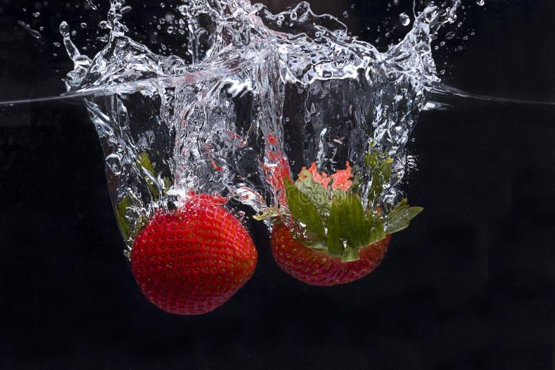 Duas morangos deixadas cair na água fotografia de stock