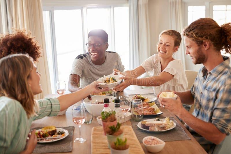 Duas mulheres adultas novas que passam um prato através da tabela de jantar durante o almoço com amigos, fim acima fotos de stock royalty free