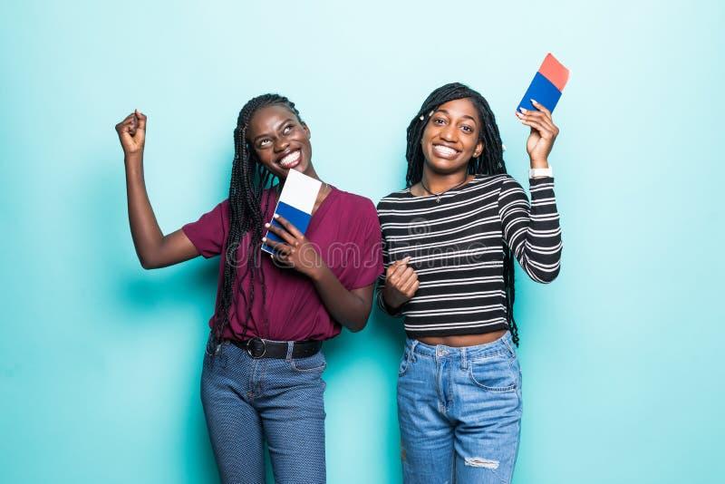 Duas mulheres africanas novas com os bilhetes do voo prontos para o curso isoladas no fundo azul pastel imagem de stock royalty free