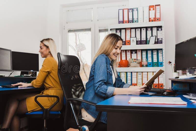 Duas mulheres alegres que trabalham com computadores fotos de stock