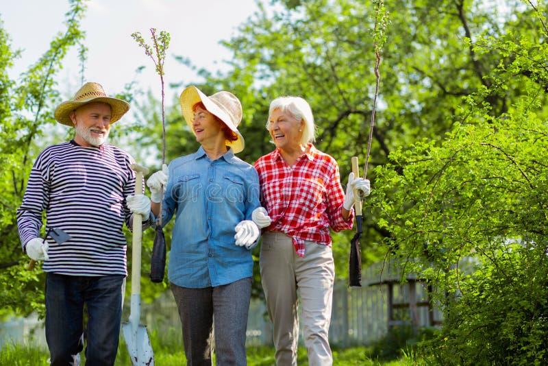 Duas mulheres aposentadas e um homem que andam ao jardim fotografia de stock royalty free