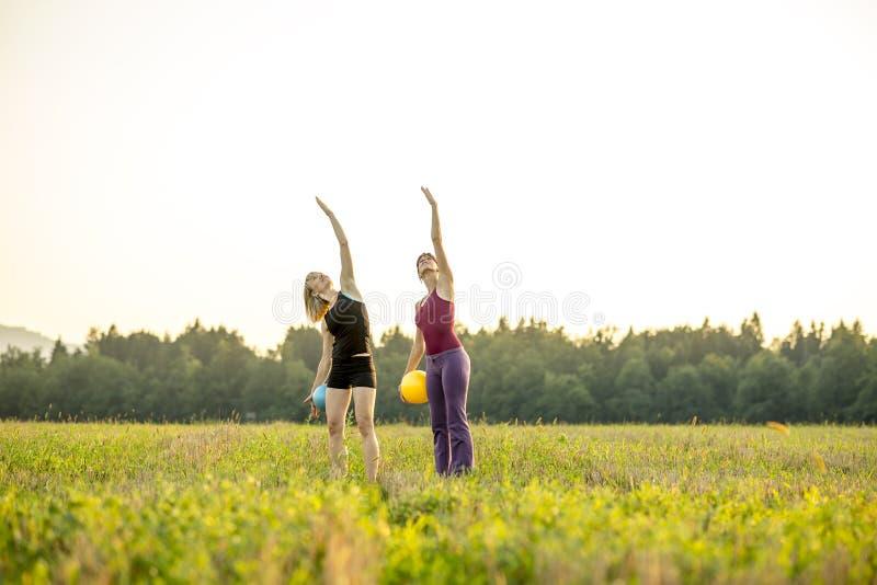 Duas mulheres aptas dos jovens que fazem pilates exercitam levantando um braço no th fotografia de stock