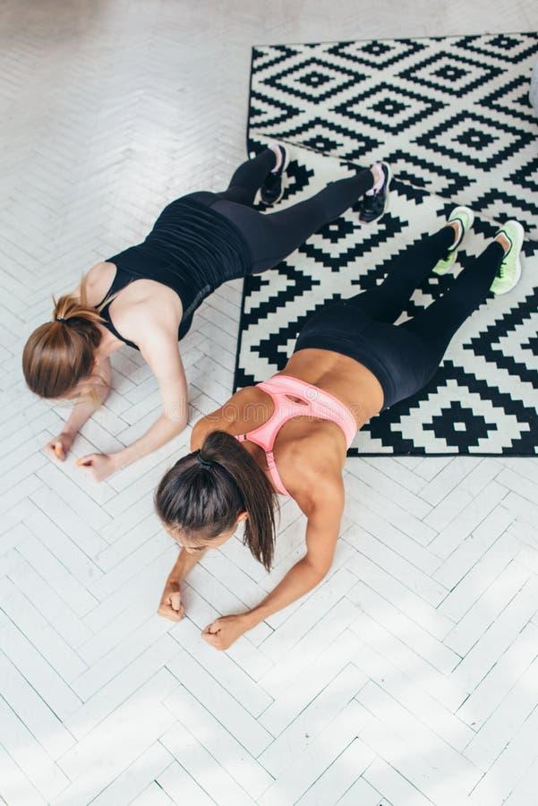 Duas mulheres aptas que fazem a prancha exercitam no assoalho em casa que treina para trás e pressionam os músculos, esporte, exe imagens de stock royalty free