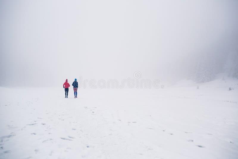 Duas mulheres arrastam o corredor na neve em montanhas do inverno foto de stock royalty free