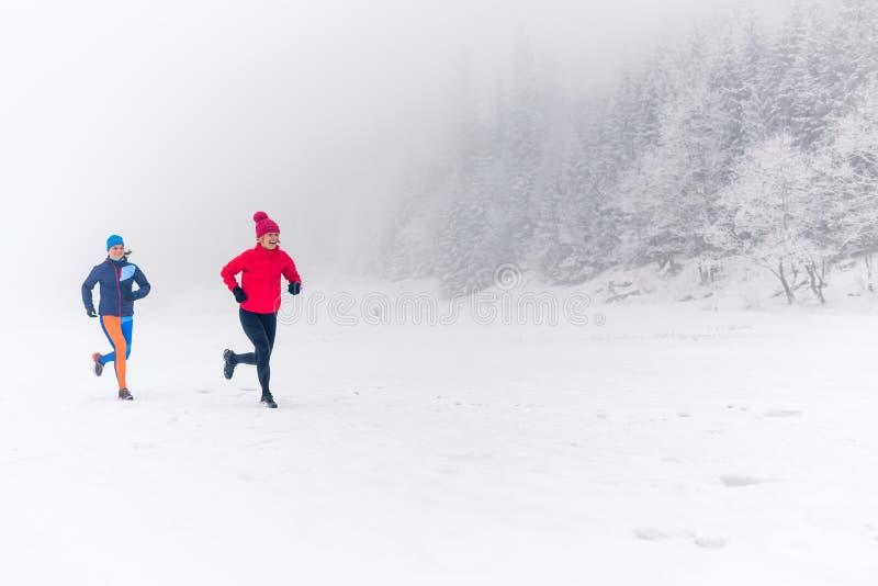 Duas mulheres arrastam o corredor na neve em montanhas do inverno imagens de stock