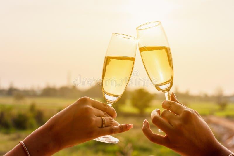 Duas mulheres asiáticas bonitas lanç o vinho branco do champange dentro com w foto de stock