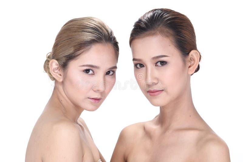 Duas mulheres asiáticas com forma bonita compõem o cabelo envolvido fotografia de stock