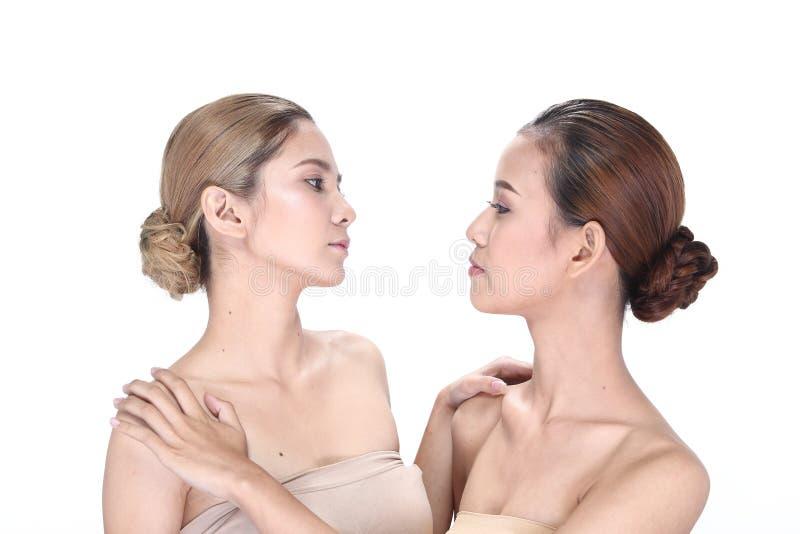 Duas mulheres asiáticas com forma bonita compõem o cabelo envolvido fotografia de stock royalty free
