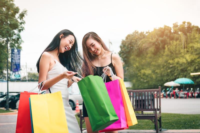 Duas mulheres asiáticas que estão na alameda da tomada e que olham dentro do shopp fotos de stock