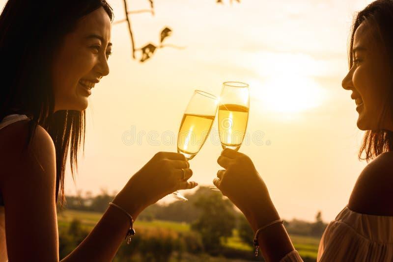 Duas mulheres asi?ticas bonitas lan? o vinho branco do champange dentro com w fotos de stock
