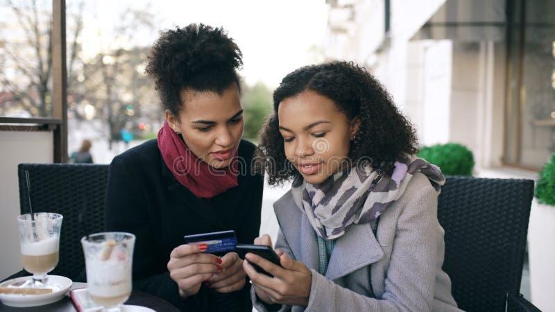 Duas mulheres atrativas da raça misturada que têm a compra em linha com cartão de crédito e smartphone ao falar e ao beber o café fotografia de stock