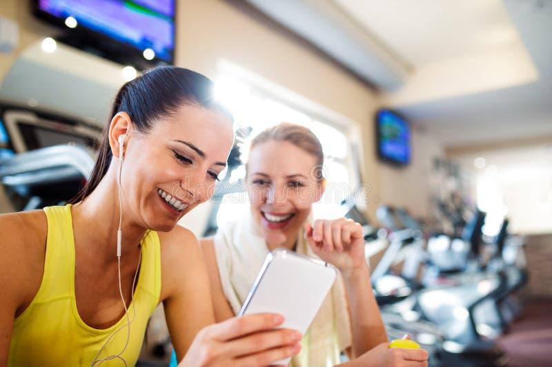 Duas mulheres atrativas do ajuste no gym com telefone esperto imagem de stock royalty free