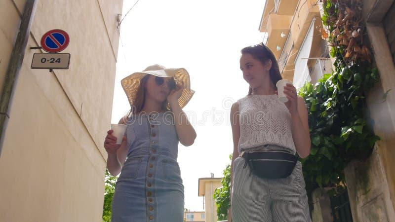 Duas mulheres atrativas que falam e para beber o café nas aleias imagem de stock royalty free