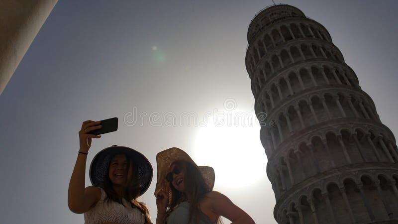 Duas mulheres atrativas tomam um selfie no fundo da torre inclinada imagens de stock