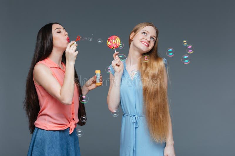 Duas mulheres bonitas alegres que comem o pirulito colorido e que fundem bolhas fotos de stock royalty free