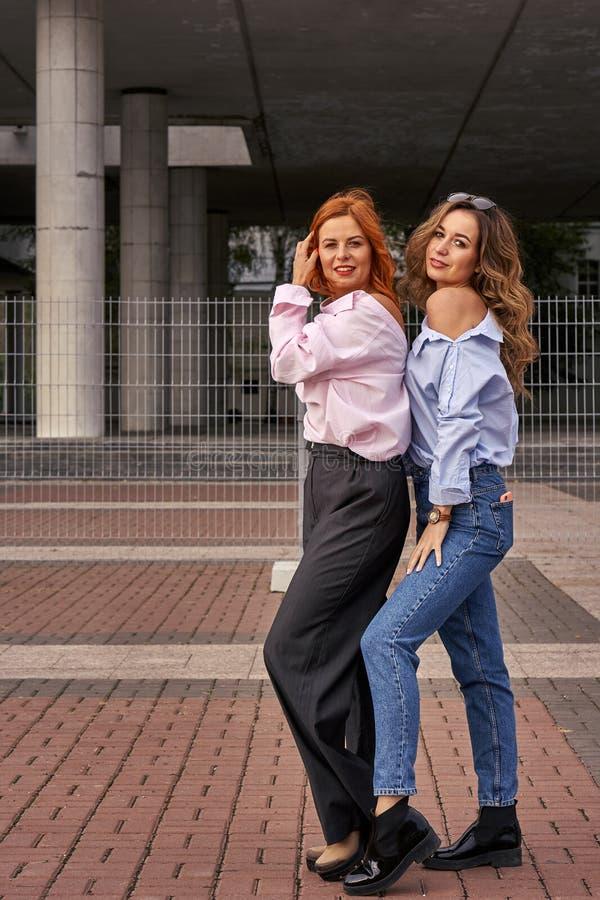 Duas mulheres bonitas com caminhada vermelha e marrom do cabelo em torno da cidade imagens de stock royalty free