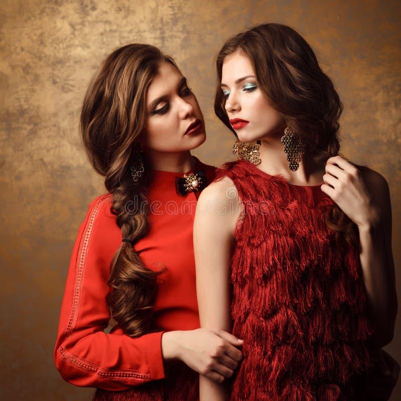 Duas mulheres bonitas em vestidos vermelhos Composição e penteado perfeitos imagens de stock royalty free