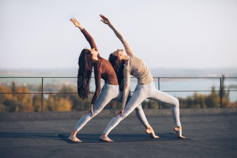 Duas mulheres bonitas executam o guerreiro dobro da pose com a mão levantada fotografia de stock